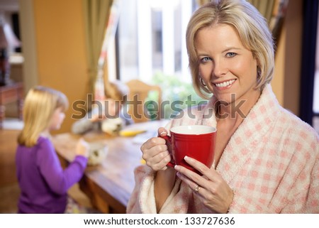 Smiling blonde Caucasian mother in foreground with her two children at the breakfast table in the kitchen, eating meal in the morning - stock photo