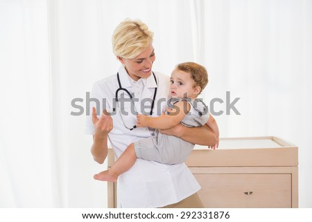 Smiling blonde doctor and child with stethoscope in the medical office - stock photo