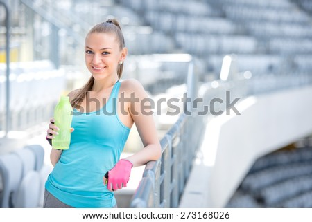 Smiling blonde fitness woman drinking water after complete outdoor workout  - stock photo