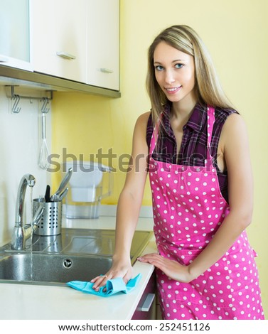 Smiling blonde girl cleaning furniture in kitchen