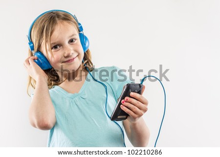 Smiling blonde girl listening to her music on smart phone in blue headphones shirt