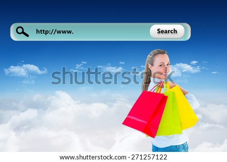 Smiling blonde holding shopping bags against bright blue sky over clouds - stock photo
