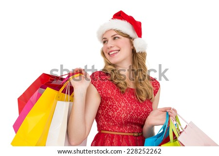Smiling blonde in santa hat holding shopping bags on white background