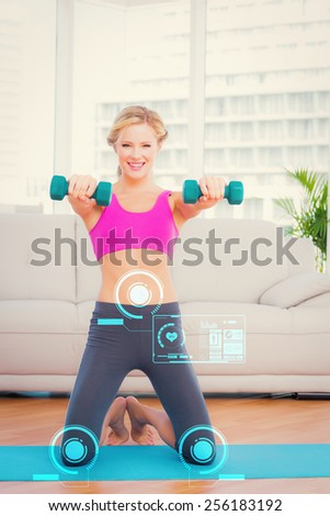 Smiling blonde lifting dumbbells on exercise mat against fitness interface - stock photo