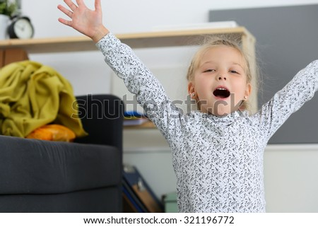 Smiling blonde little girl raised up hands near couch hailing and looking in camera. Cute positive female child posing portrait. Kid playing games using imagination. Family concept