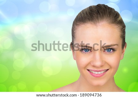 Smiling blonde natural beauty against green and blue abstract design - stock photo