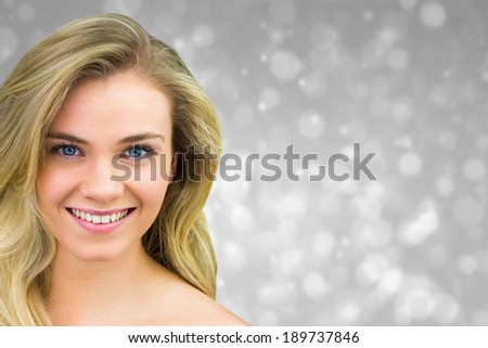 Smiling blonde natural beauty against grey abstract light spot design - stock photo