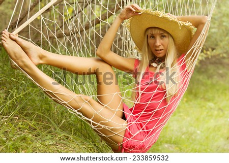 Smiling blonde relaxing on hammock in garden - stock photo