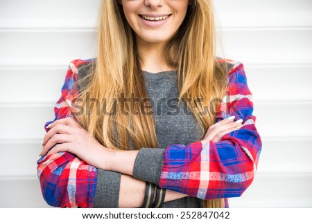 Smiling, blonde, trendy girl is posing on white background.