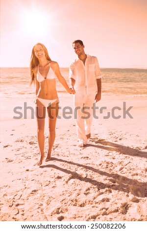 Smiling blonde walking away from man holding her hand on the beach - stock photo
