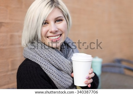 Smiling blonde woman drinking coffee outdoor at cafe - stock photo