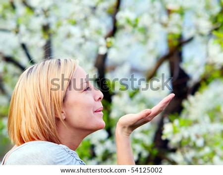 Smiling blonde woman enjoying spring - stock photo