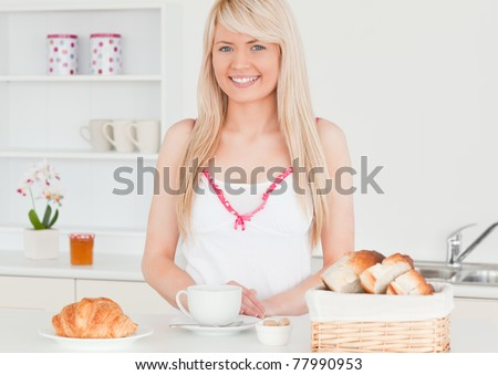 Smiling blonde woman having her breakfast in the kitchen in her appartment