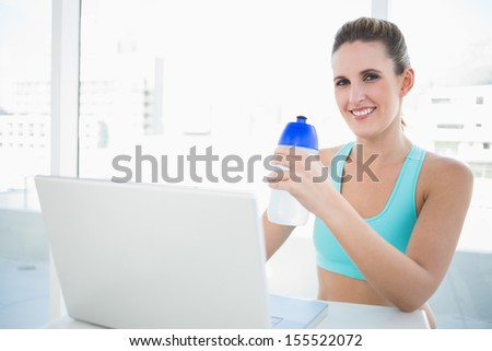 Smiling blonde woman in sportswear holding flask while working on laptop - stock photo