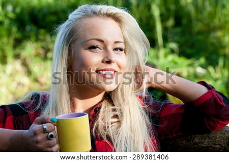 smiling blonde woman in the nature drinking a tea or a coffee from her mug - stock photo