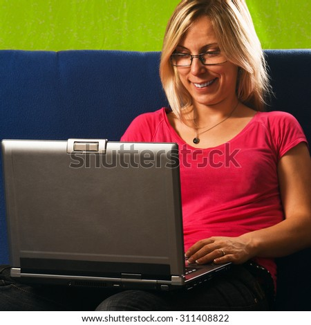 Smiling blonde woman is typing on laptop.