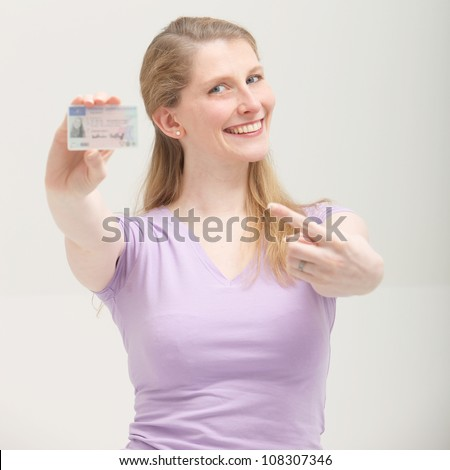 Smiling blonde woman pointing on her ID card Smiling blonde woman pointing on her ID card - isolated on white