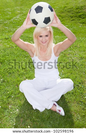 Smiling blonde woman sitting on green grass holding a soccerball or football above her head - stock photo