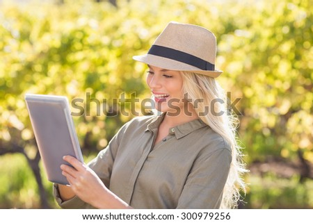 Smiling blonde woman using a tablet in the countryside - stock photo