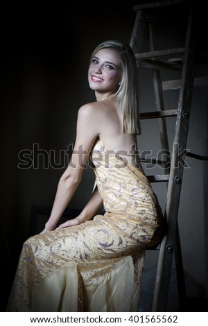 Smiling blonde woman wearing sexy gold evening dress seated on a ladder in the dim twilight. - stock photo