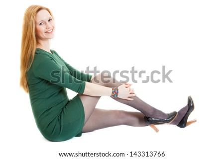 smiling blonde young woman wearing a green dress, black panti-tights and black sandals