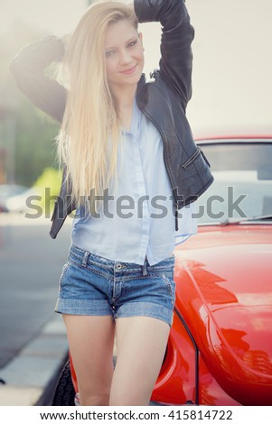 smiling blonde young woman with red old car in a cityscape - stock photo