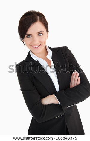 Smiling blue eyed woman in suit with arms folded against white background