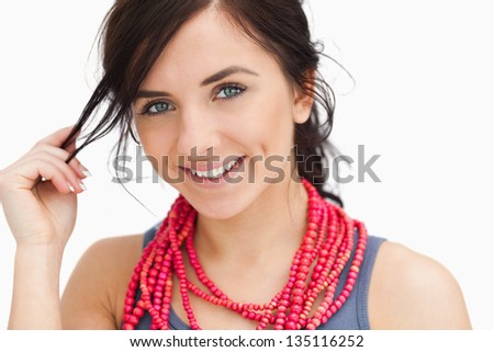 Smiling blue eyed woman with a red bead necklace against white background