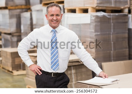Smiling boss leaning on stack of cartons in a large warehouse - stock photo