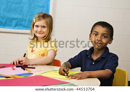 Smiling boy and girl doing projects in art class. Horizontally framed shot. - stock photo