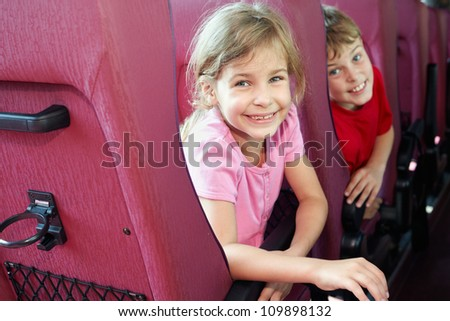 Smiling boy and girl look out from backs of seats in bus - stock photo