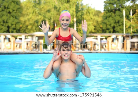 Smiling boy and girl playing in the outdoor swimming pool and waving their hands - stock photo