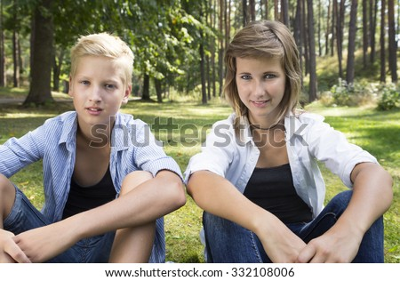 Smiling boy and girl (siblings) sitting on the green grass in nature sunny day. Concept of positive thoughts and emotions. - stock photo