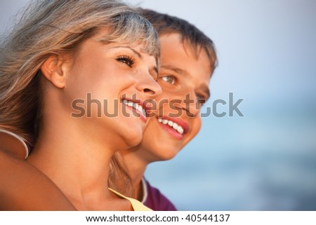 smiling boy and young woman on beach in evening, Looking afar - stock photo