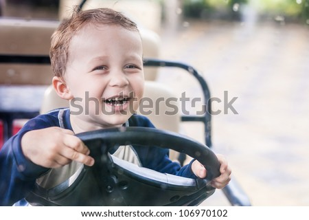 Smiling boy behind the wheel of the electric vehicle - stock photo