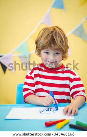Smiling boy colouring some paper at the desk - stock photo
