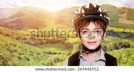 smiling boy cyclist over mountains background collage - stock photo