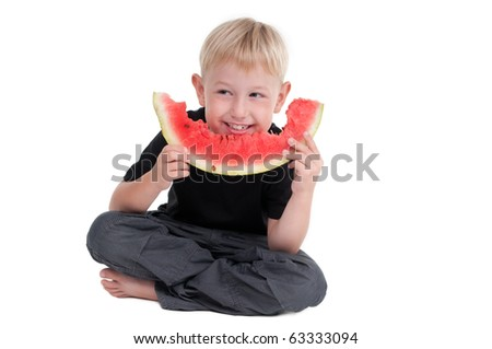 Smiling boy eating a slice of water melon - stock photo