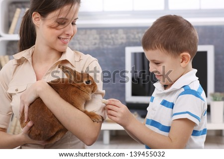 Smiling boy feeding cute pet rabbit handheld by happy young mother. - stock photo