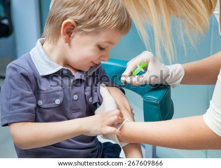 smiling boy getting his vaccination injection  - stock photo