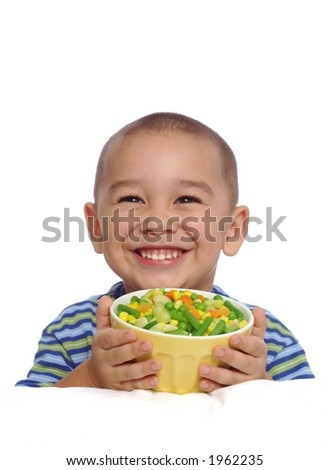 Smiling boy holding a bowl of mixed vegetables
