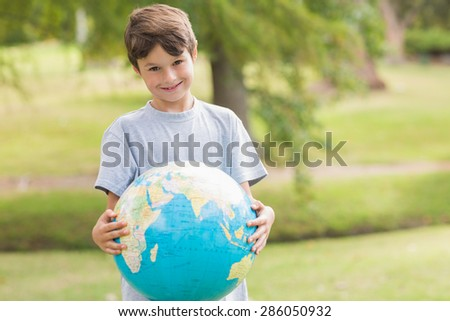 Smiling boy holding an earth globe in the park on a sunny day - stock photo