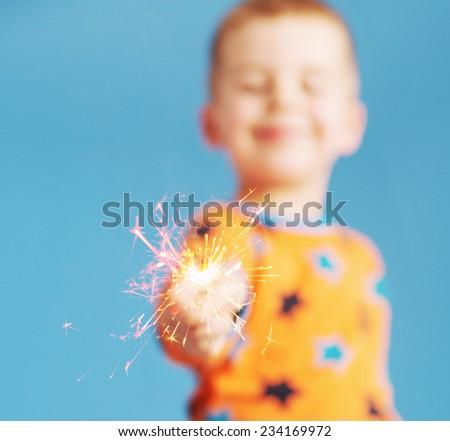 Smiling boy holding fireworks - stock photo