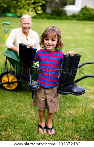 Smiling boy holding wellington boots while standing in yard