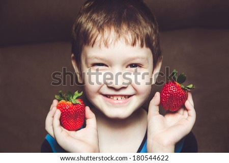 Smiling boy holds a strawberry in hands on chocolate background. - stock photo