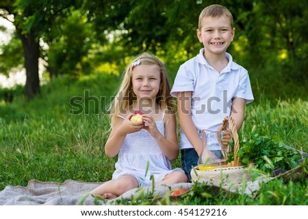 Smiling boy holds picnic basket and a girl eats apple sitting on the grass