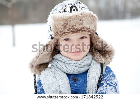 Smiling boy in a warm clothing in the snow - stock photo