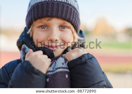 Smiling boy in autumn day looking at camera - stock photo