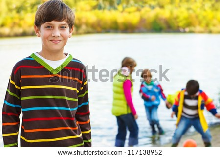 Smiling boy in front, and his friends playing with a ball in lake - stock photo