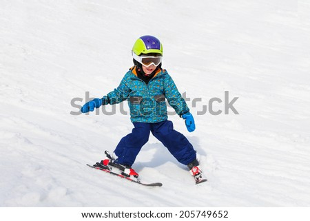 Smiling boy in ski mask learns skiing - stock photo